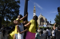 Children visiting from Colombia cling to a light pole to get a better view of where Pope Francis is celebrating a Mass of Canonization of Blessed Junipero Serra at the Basilica of the National Shrine of the Immaculate Conception /  Catholic University of America in Washington, D.C.  on Wednesday, September 23, 2015.