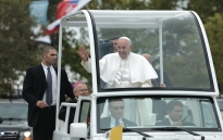 Pope Francis waves to a crowd along the Benjamin Parkway in Philadelphia.