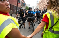 Members of the Minnesota Immigrant Rights Action Committee hold hands to control how close the police officers can get to protesters marching at the Republican National Convention on Monday, July 18, 2016 in Cleveland. (Photo by Antonella Crescimbeni)