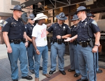 Joseph Offutt ,from Dallas, greets Indiana State Police officers in downtown Cleveland during the Republican National Convention Tuesday, July 19, 2016. Offutt is a member of Kindness 365, an organization that inspires people to spread compassion. (Photo by Gabrielle Mannino)