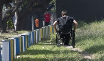 Penn State student Brett Gravatt navigates a dirt path along a sidewalk in Rio de Janeiro on Monday, Sept. 12, 2016. The broken stones and tree roots made the sidewalk inaccessible to wheelchairs forcing Gravatt to the dirt path. (Cameron Hart/Penn State University via AP)