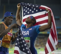 David Brown holds an American flag aloft as he and his sighted guide, Jerome Avery, celebrate Brown's Paralymic record time of 10.99 seconds in the 100 meter dash at the 2016 Paralympic Games at Olympic Stadium in Rio de Janeiro, on Sunday, Sept. 11, 2016. (Antonella Crescimbeni/Penn State University via AP)