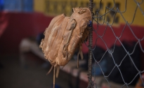 A baseball glove hangs from the fence at a baseball field in Juan Diaz, Panama, where PTY Baseball Academy practiced on March 9.