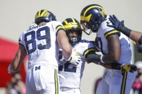 Michigan running back Karan Higdon, center, celebrates a touchdown with teammates Ian Bunting, left, and Tyrone Wheatley during the second half of an NCAA college football game against Indiana in Bloomington, Ind., Saturday, Oct. 14, 2017. Michigan won 27-20 in overtime. (AP Photo/AJ Mast)