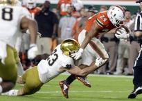 FILE - In this Nov. 11, 2017, file photo, Notre Dame linebacker Drue Tranquill (23) tries to tackled Miami running back Travis Homer (24) during the second half of an NCAA college football game in Miami Gardens, Fla. Notre Dame's turnaround season took a detour last week. The ninth-ranked Fighting Irish have no time to wallow in misery, either, not with Navy visiting on Saturday. Navy brings a triple-option offense with lots of history to South Bend, and will test a defense that couldn't contain Miami in a 41-8 rout. (AP Photo/Lynne Sladky, File)