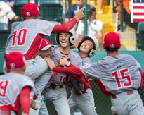Japan's Seiya Arai (14) is embraced by Kazuki Watanabe (8) and Ryuto Inoue (5) after he scored the winning run to defeat Southwest in the 2017 Little League Baseball World Series Championship game against Southwest at Lamade Stadium on Sunday, Aug. 27, 2017. Japan defeated Southwest 12-2 in five innings.