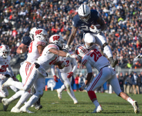 Penn State running back Miles Sanders (24) leaps over Wisconsin defenders Eric Burrell (25) and D'Cota Dixon (14) during their game at Beaver Stadium. Penn State defeated  Wisconsin 22-10. Sanders had 23 carries for 159 yards and one touchdown.