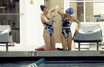 Jessica Long, left, helps a fellow ability athlete to stretch out before a training session at the pool.