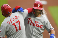 Philadelphia Phillies' Rhys Hoskins and Bryce Harper celebrate Harper's home run during a baseball game against the Atlanta Braves, Saturday, Aug. 22, 2020, in Atlanta. (AP Photo/John Amis)