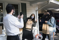 From left, Rabbi Hershy Gourarie takes a photo of his wife Miri Gourarie with Penn State students, Emily Sachs and Paige Goldstein, as they pick up their Shabbat-to-go bags on October 16, 2020 outside their home in State College.
