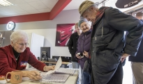 Glen Mower checks in with his wife, Anne, to cast their vote in the 2012 Presidential election at Mike's Video, TV & Appliance in State College. Glen and his wife have been voting for over 70 years.