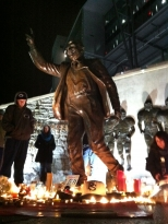 Students stand next to an impromptu shrine created at the base of the Joe Paterno statue outside of Beaver Stadium Saturday evening amidst rumors of the legendary football coach's imminent demise. The Paterno family said Paterno is still alive, but he is hospitalized and his health is fragile.