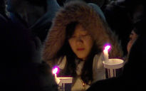 A student holds a candle at Joe Paterno's statue Saturday night