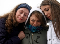 Members of the Penn State show choir group Singing Lions, from left, Annelise Gaus, Meredith Moore and Tanya Cuadra huddle together after singing the Penn State alma mater at the Joe Paterno statue outside of Beaver Stadium hours after learning that Coach Paterno had died.