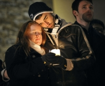 Katie Knobloch (senior-elementary education) and Andrew Adamietz (sophomore-secondary english education), both members of Blue in the Face singers, embrace on the stairs of Old Main on Sunday night during the candlelight vigil in memory of Joe Paterno, who died Sunday morning.