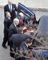 Pallbearers slide the casket of former head football coach Joe Paterno into a hearse outside of the Pasquerilla Spiritual Center before the funeral procession through the University Park campus and State College on Wednesday afternoon. The pallbearers included Paterno's grandson, Joe Jr., top right, his son Scott, center right, touching casket, and son Jay, lower right.