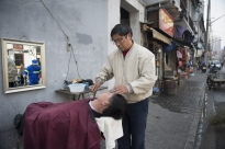 A barber in a residential neighborhood of Shanghai offers shaves using a straight razor.