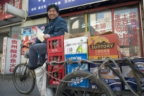 "Dong Yan, 46, learned how to ride a bicycle in elementary school. For the past three years, he's made his living on this tricycle, which includes a six-foot flatbed that carries up to 16 cases of beer or soft drinks. He makes 10 deliveries a day, each trip about 40 minutes through the back alleys and smaller streets of the city.  These slow, bulky bikes are typically not welcome on the fast-paced main streets. ""I don't get too sore from peddling and it is not too hard to balance,"" Dong said. ""But I get fatigue from carrying the beverages to the stores."""