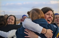 Former Penn State soccer player Katie Schoepfer, far left, hugs Student Athlete Advisory Board (SAAB) dancer Meghan Gill, while former Penn State soccer player Megan Monroig hugs SAAB dancer Krissy Tribbett on Friday afternoon as the dancers walk through the human tunnel leading into THON 2012