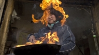 Zhou Zhongqun cooks a meal in front of the one-room residence that serves as her family's home and restaurant business.