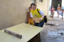 Jen Swales plays ping pong using a paddle and table made from construction scraps in the Jacaré favela.