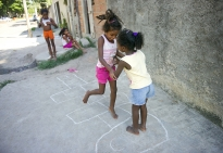 From right,  sisters Joyce, 6, and Raissa, 7, giggle and embrace during a game of hopscotch while cousin Maria Eduarda, 6, and sister Thamires, 10 watch in the background. The girls live in Vila Autodromo in Rio de Janeiro, Brazil. The city is trying to relocate the people who live in the favela because it lies in an area slated for redevelopment prior to the 2016 Olympic games.