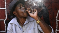 Dennys Garcia Reys smokes a Cuban cigar in a bar in Havana. Reys works in a hospital, and because he is paid 500 Cuban ordinary pesos a month, he cannot afford to smoke Cuban cigars on a regular basis.