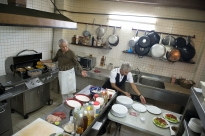 Chef Erasmo Hernandez, left, owner and executive chef of Mama Ines, a private restaurant in Old Havana, reaches to his sous-chef for a plate for fried plantain chips on March 11, 2014. Hernandez worked as Fidel Castro's chef before retiring and opening his own restaurant.