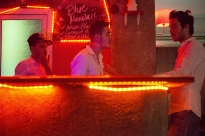 Dayan Marin Garcia, middle, and Ernesto Lusson, right, both employees, wait at the bar for customers to enter Humboldt, a gay bar in the Vedado municipality of Havana, on Wednesday, March 12, 2014.