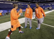 East Carolina quarterback Shane Carden, left, jokes with Nevada quarterback Cody Fajardo (5) and UCLA quarterback Brett Hundley before stretching at the NFL football scouting combine in Indianapolis, Saturday, Feb. 21, 2015. (AP Photo/David J. Phillip)
