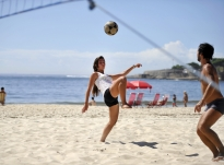 A female futevôlei player knees the ball over the net on post 6 at Copacabana Beach during a two-on-two match with a coed partner. Games and practices typically run Monday, Wednesday and Friday mornings, and then again in the late evening.