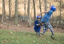 Ten-year-old Deven Jackson, right, hands off the football to his brother, Bentley, 3, in the backyard of their home in Perry County, Pa. In 2012 Deven was diagnosed with bacterial meningitis and had both of his legs amputated below the knee.  After many months of recovery, Deven is able to play football again.