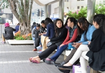 Domestic helpers socialize around Central Mass transit Railway (MTR) Station Exit K in Hong Kong's Statue Park. On their day off, which is usually on Saturday or Sunday, many domestic helpers meet friends around the city.