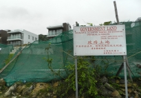 In the Tai Tan village, government signs attempt to fend off builders, yet brand new homes sit in the background. Many people are critical of the government for not doing enough to prevent the development of these enclave villages, which are in biologically diverse natural areas of Hong Kong.