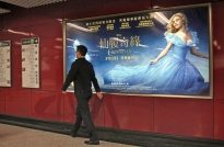 "In the Mass Transit Rail (MTA) station in Kowloon Tong, Hong Kong, a display advertises the Hollywood film ""Cinderella"" as travelers pass by. Advertisements for Hollywood films have become very popular in Hong Kong."