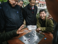 A group of men play a game of Chinese chess known as 'Xiangqi' in a park in Sheung Shui, a town on the Northern border between Hong Kong and China.
