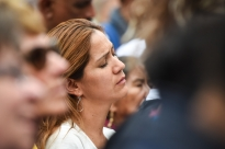 A woman listens to a hymn during Mass Sunday afternoon in Philadelphia. /photo by Cameron Hart